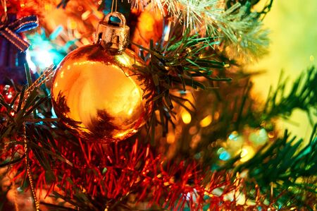 Artificial christmas tree with toys, garlands and lights. Shiny christmas gold ball hanging on pine branches.