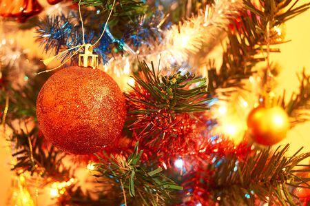 Artificial christmas tree with toys, garlands and lights. Shiny christmas red ball hanging on pine branches.