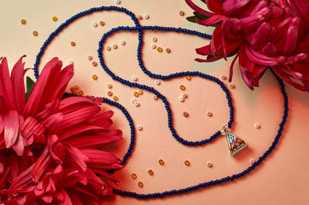 Handmade beadwork, beading as a hobby. Decorations made with your own hands on the background of various flowers and plants.