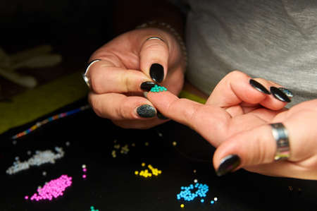 the girl makes beadwork, beading as a hobby. Jewelry made with your own hands