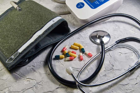 a stethoscope and heart-shaped pills. Concept of treatment of heart diseases 免版税图像