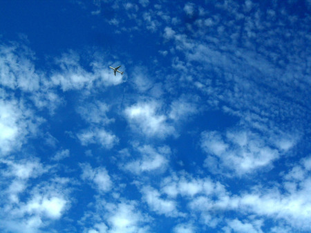 skyscapes: plane crossing a blue sky among white fluffy clouds