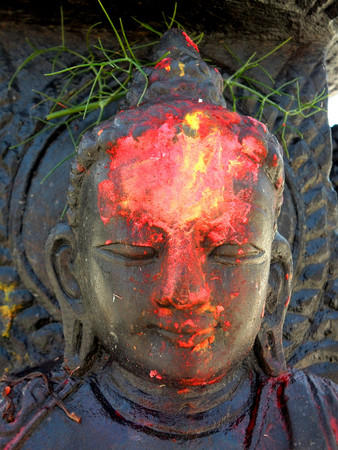devotions: red paint on a buddha statues forehead in Nepal