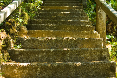Stairway of concrete stairs leading up with sun shining on them 版權商用圖片