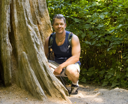 Man crouching next to old tree in gravel with leaves behind him