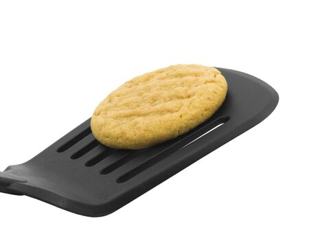 Peanut butter cookie on a spatula with white background Imagens