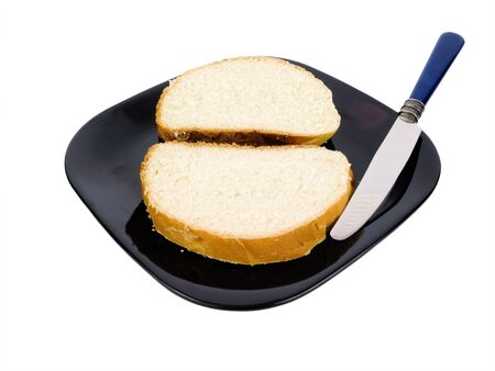 Sliced bread on a black plate with knife