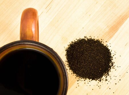 coffee grounds: coffee grounds with mug on a wooden background