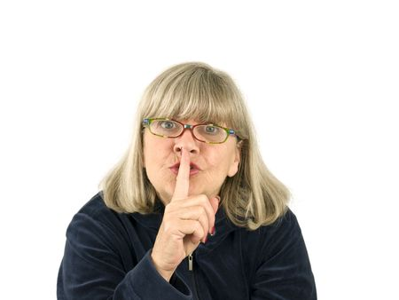 Senior woman with finger to lips on a white background
