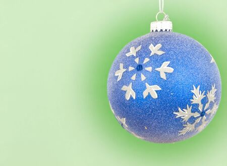 Blue bauble ornament hanging with green background
