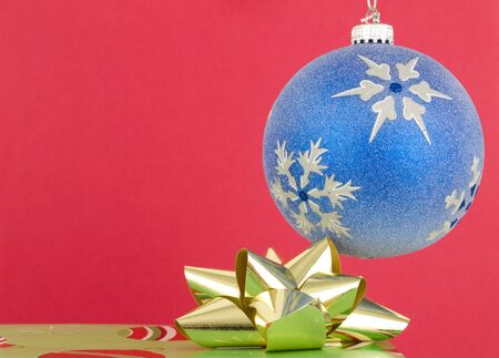 Christmas ornament and present on a red background