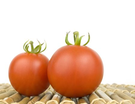 Two Ripe Tomatoes on bamboo with white background