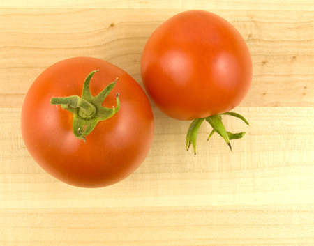Two ripe tomatoes on a wooden background Imagens