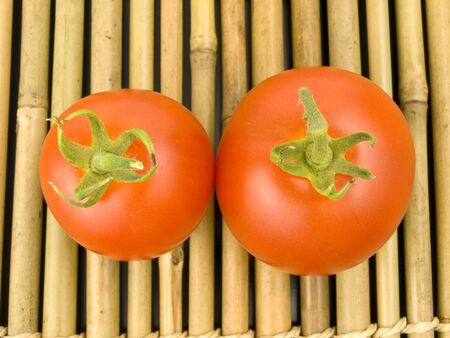 Two tomatoes on a wooden bamboo background