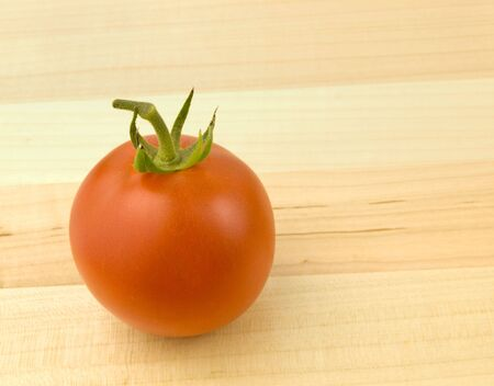 Single Ripe Tomato on a wooden background Imagens