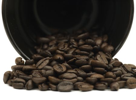Close up of coffee mug spilling beans on a white background