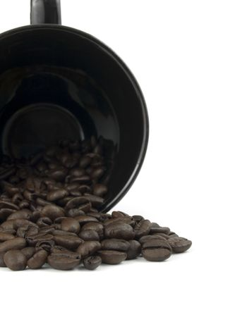 Black mug spilling roasted coffee beans on white Imagens