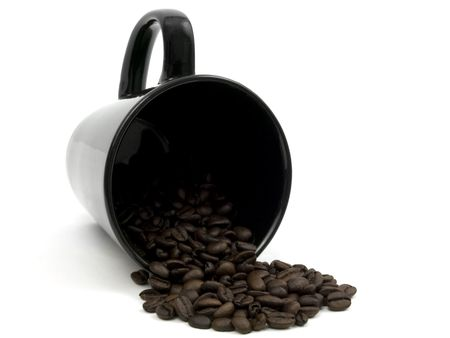 black mug spilling coffee beans on a white background