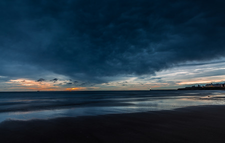 A cloudy start to the day at Tynemouth Longsands as the sun rises on the horizon