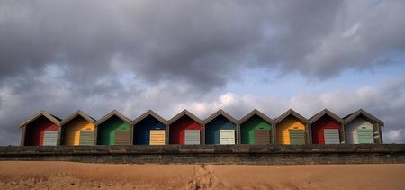 Colourful Beach huts by the beach against a cloudy blue sky Stock Photo