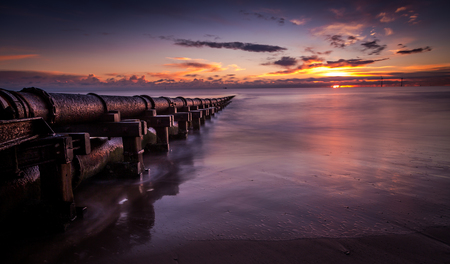 An old rusty pipe heads off out to sea, taken at sunrise Stockfoto