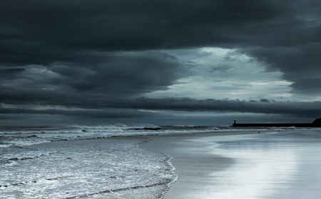 A cloudy stormy morning at the beach, as the morning sun tries to break through the clouds