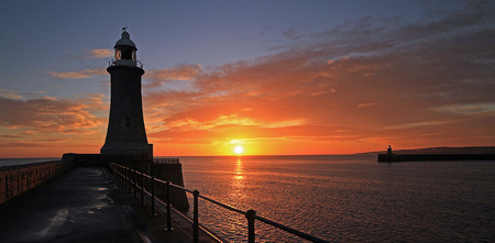 The sun rises on a cloudy morning in between the piers at the mouth of the River Tyne. Stockfoto
