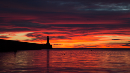 A beautiful start to the day pre-dawn down at Priors Haven in Tynemouth, with the pier & lighthouse silhouetted against the morning sky Stockfoto