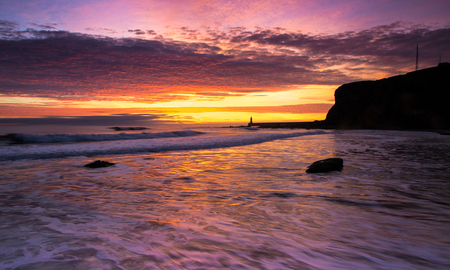 Sunrise at King Edwards Bay, Tynemouth in the North East of England, looking towards the North Pier at the mouth of the River Tyne.