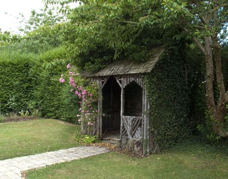 Wooden Summer House with Ivy Growing Over Side
