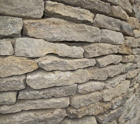 A closeup of a cotswold dry stone wal.  The wall is on a corner.....