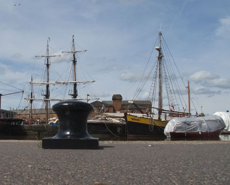 Tall ships pictured in the background of an anchor point at Gloucester Docks, England