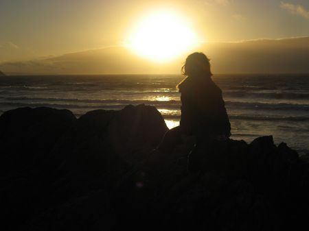 A glous sunset with girl sat on the rocks Stock Photo - 5357527