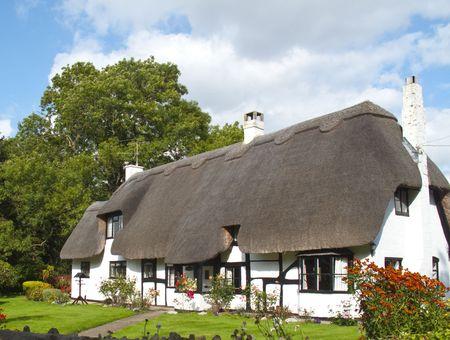 una postal preciosa casa de campo con techo de paja blanca Editorial