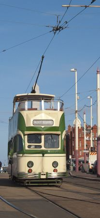 a green and white tram at blackpool north pier