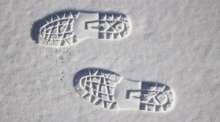 a couple of deep footprints in the snow
