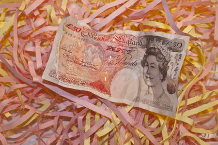 a fifty pound note on topof some shredded paper