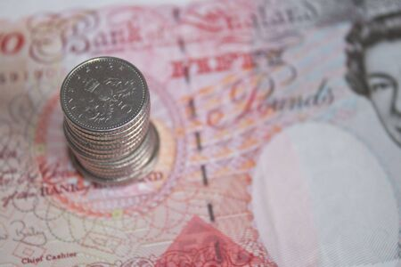 some five pence pieces stacked on top of a fifty pound note in soft focus