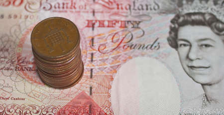 some one pence pieces stacked on top of a fifty pound note in soft focus photo