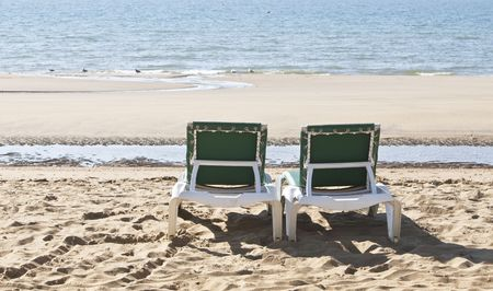 two deckchair recliners on the beach overlooking the sea