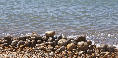 some pebbles stacked up on a pebbly beach close to the waters edge