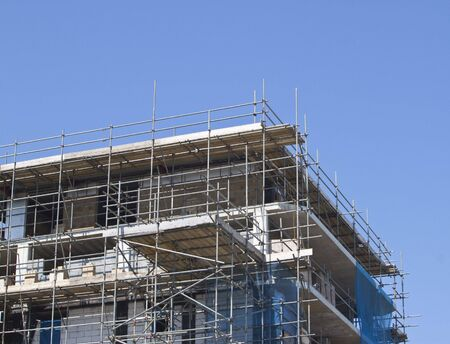 a construction site with scaffolding surrounding against wonderful blue sky Stock Photo