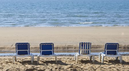 three blue, one stripped sun loungers over looking a blue sea Stock Photo