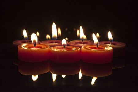 some red and purple candles lit and glowing on a black background Stock Photo