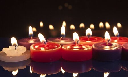 some red, white and purple candles glowing against a black background Stock Photo