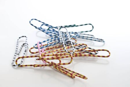 a pile of multi paper clips of different colours on white with type space