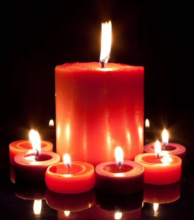 a large red candle surrounded by small red and purple