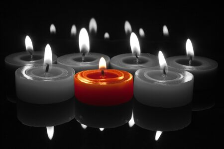 glowing flames from centre red candle with reflections top and bottom