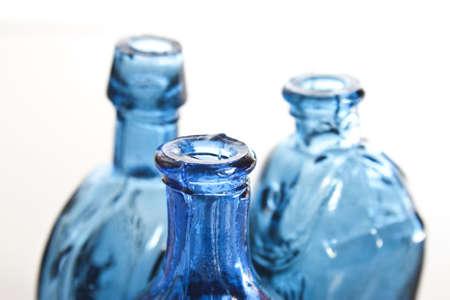 three blue vintage bottles with soft focus on front bottle