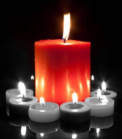 a large red candle surrounded by small in black and white